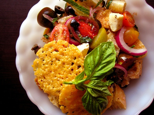 panzanella salad with crispy rounds of parmesan cheese